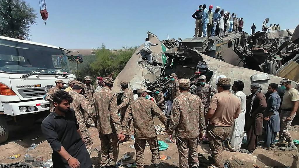 Truppen der pakistanischen Armee und Rettungskräfte sind am Ort der Zugkollision im Einsatz.