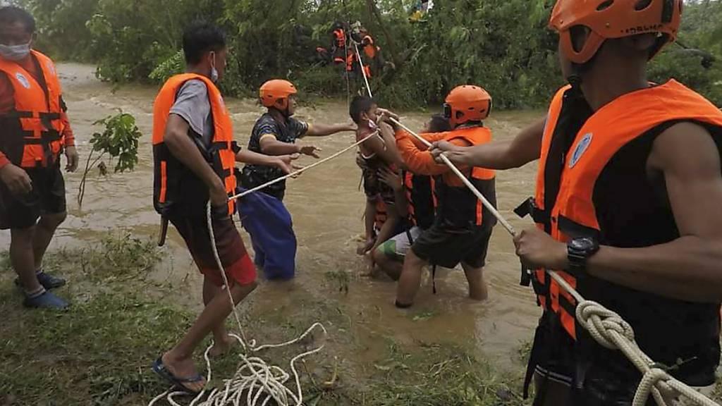 HANDOUT - Auf diesem vom Gonzaga Municipal Disaster Risk Reduction and Management Office veröffentlichten Foto helfen Rettungskräfte einem Kind während der Evakuierung durch einen Fluss. Ein schwerer Tropensturm hat auf den Philippinen Erdrutsche und Sturzfluten ausgelöst. Foto: Uncredited/PHILIPPINE COAST GUARD/AP/dpa - ACHTUNG: Nur zur redaktionellen Verwendung und nur mit vollständiger Nennung des vorstehenden Credits