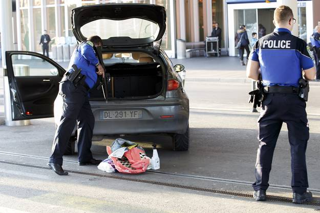 Polizeibeamte kontrollieren ein Fahrzeug beim Flughafen.