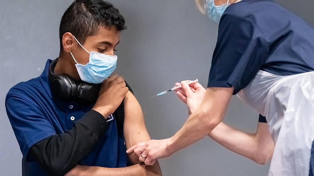 Die Krankenschwester Sonia Wilson (r) impft den 18-jährigen Cameron Ladd mit dem Corona-Impfstoff von Biontech/Pfizer in einem Massenimpfzentrum in Doncaster. Foto: Danny Lawson/PA Wire/dpa