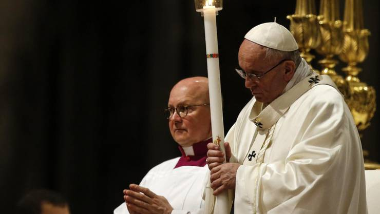 Papst Franziskus mit einer Kerze während der Messe.