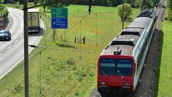 Ein Triebwagen der OeBB, unterwegs auf dem sanierungsbedürftigen Streckenabschnitt vor der Oensinger Dünnernbrücke (hinten rechts).