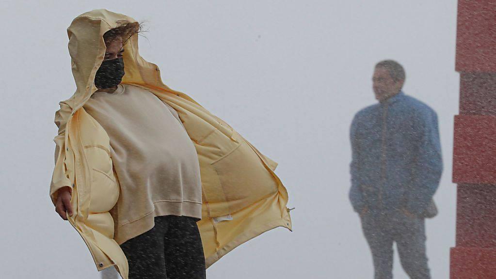 dpatopbilder - Eine Frau kämpft bei Regen gegen den starken Wind in Nizza an. Nach Unwettern und Überschwemmungen in der Region der südfranzösischen Metropole werden nach Medienberichten mindestens neun Menschen vermisst. Foto: Valery Hache/AFP/dpa