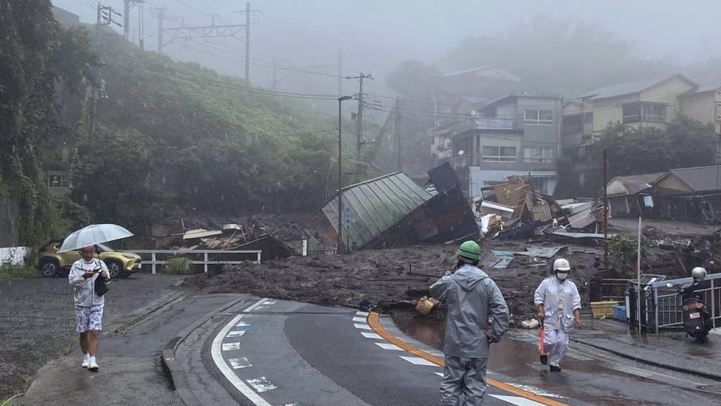Eine Strasse ist nach starkem Regen mit Schlamm, Geröll und Trümmern bedeckt. Eine enorme Schlammlawine infolge schwerer Regenfälle hat in Japan mehrere Wohnhäuser zerstört.