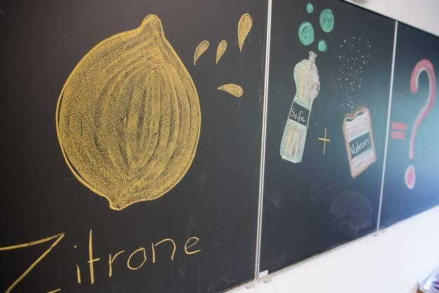Seit der letzten Lexionsstunde wissend die Kinder, dass Backpulver in einer Zitrone vermengt mit Flüssigseife einen kleinen Vulkan ergibt.