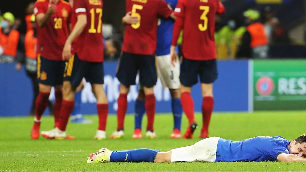 Italiens Federico Chiesa liegt enttäuscht im Rasen, während sich die Spanier dahinter über ihren Finaleinzug freuen