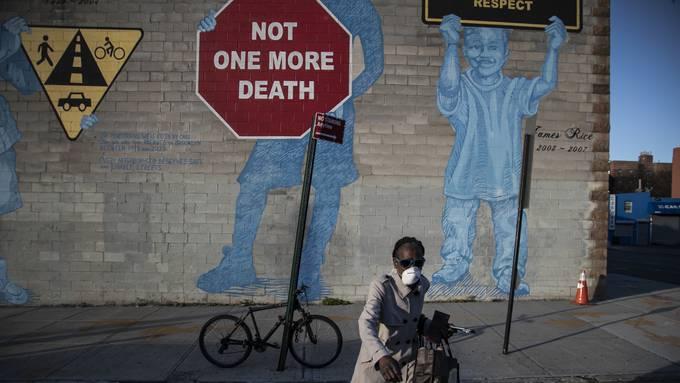 Frau mit Schutzmaske in Brooklyn, New York. Die USA verzeichnet den höchsten Anstieg an Coronafällen. Die Kritik an der Regierung ist laut.
