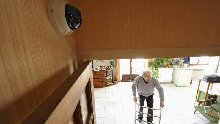 Eine Kamera filmt den Wohnbereich eines älteren Mannes. Der Zuschauer kann bei einem Notfall schnell einen Alarm auslösen.
