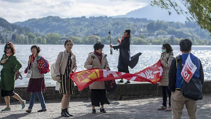 Die chinesischen Touristen posieren vor der idyllischen Kulisse.