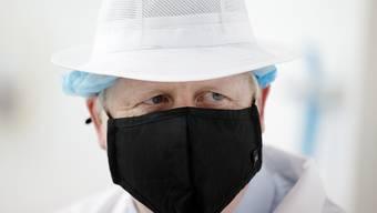Boris Johnson, Premierminister von Großbritannien, trägt Schutzkleidung und einen Mundschutz bei einem Besuch der Orkney Cheese Company. Foto: Robert Perry/PA/dpa