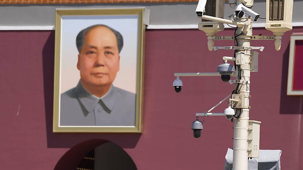 Sicherheitskräfte in Zivil beobachten, wie Touristen das Tian'anmen-Tor am 32. Jahrestag der blutigen Niederschlagung der Demokratiebewegung besuchen. Zum Jahrestag des Massakers am 4. Juni 1989 in China haben Familien der Opfer eine gerechte Aufarbeitung dieses dunklen Kapitels der chinesischen Geschichte gefordert. Foto: Ng Han Guan/AP/dpa