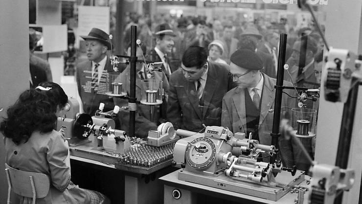 Besucher und eine Arbeiterin in der Maschinenhalle an der Mustermesse im Jahr 1960. (Archivbild)