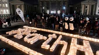 Hier im Bild: Kerzen brennen vor dem im Dunkeln stehenden Brandenburger Tor in Berlin: Zur Earth Hour wurden in über 7000 Städten die Lichter an Sehenswürdigkeiten ausgeschaltet. Im Zeichen des Klimaschutzes.