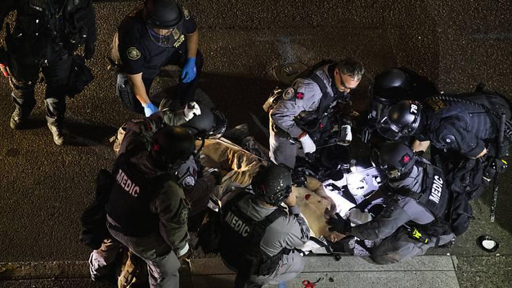 dpatopbilder - Ein Mann wird von Sanitätern behandelt, nachdem er erschossen wurde. Am 29.08.2020 brachen in der Innenstadt von Portland Kämpfe aus, als ein Autokorso der Anhänger von US-Präsident Donald Trump durch die Stadt fuhr und mit Gegnern zusammenstieß. Foto: Paula Bronstein/FR171772 AP/dpa