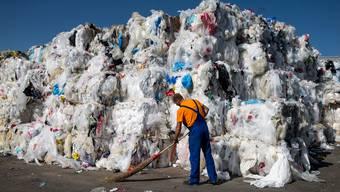 Ein Mann wischt vor einem Abfallberg aus Plastik, fotografiert am Mittwoch, 22. August 2018, bei InnoRecycling AG in Eschlikon. Aus den sortenreinen Kunststoffen stellt man hochwertige Recyclingkunststoffe (Regranulate) fuer neue Produkte her. (KEYSTONE/Alexandra Wey)