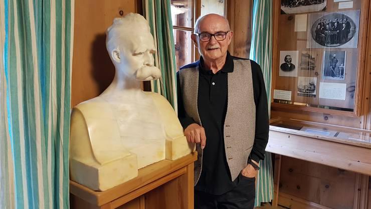 Peter André Bloch im Ausstellungsraum zu Nietzsches Leben im Nietzsche-Haus in Sils-Maria. Neben ihm steht eine Nietzsche-Stele von Max Kruse, Marmor, 1899