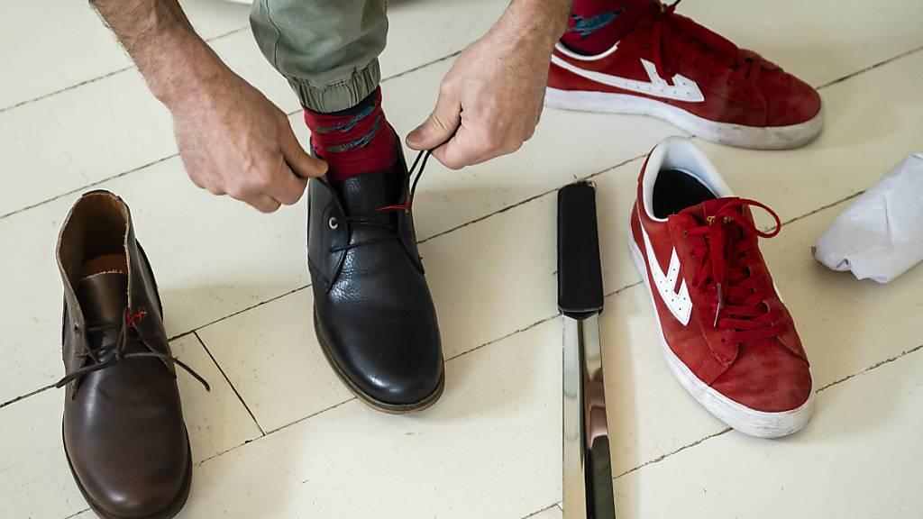Endlich wieder im Laden einkaufen: Ein Kunde probiert in einem Schuhgeschäft in Lausanne ein Paar Schuhe an.