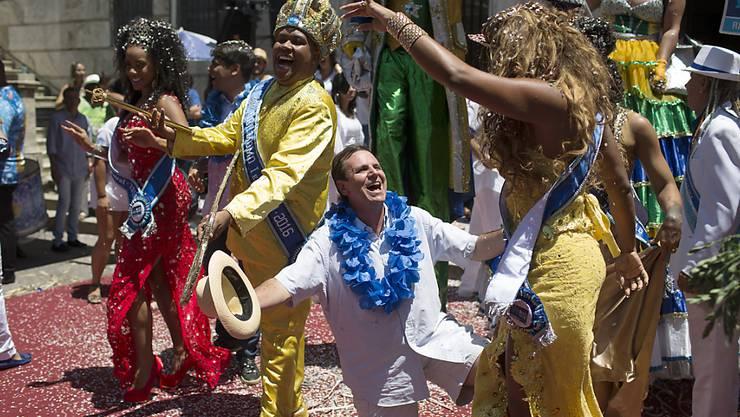 """Nach der Schlüsselübergabe kniet Rios Stadtpräsident Eduardo Paes vor einer tanzenden Karnevals-Prinzessin. Links von Paes ist """"König Momo"""" mit dem Schlüssel."""