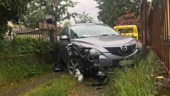 Das Auto kollidiert erst mit einem Fussgänger und prallt dann in ein Eisentor einer Hauszufahrt.