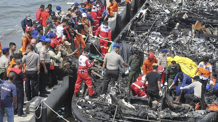 Rettungskräfte suchen im ausgebrannten Wrack nach weiteren Opfern.