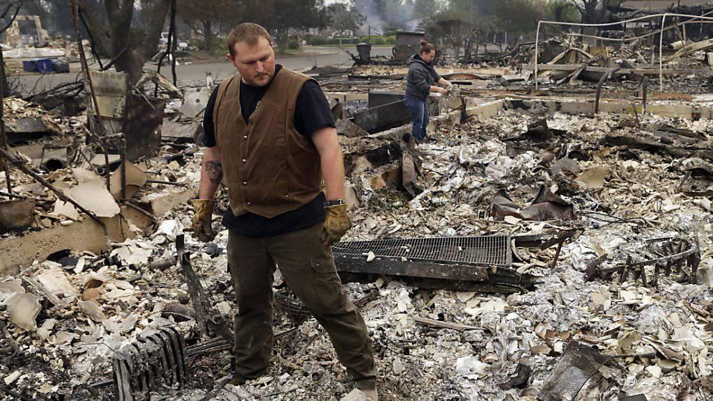 Anwohner begutachten, was nach dem Brand von ihrem Haus übrig geblieben ist.