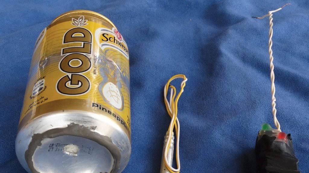 Auf dem Bild ist eine Dose des Erfrischungsgetränks Schweppes Gold zu sehen sowie Bauteile, die ein Zünder und ein Schalter sein könnten.