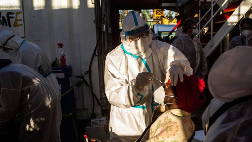 Mitarbeiter des Seenotrettungsschiffs «Ocean Viking» führen an geretteten Migranten Coronatests durch.