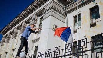 Ein Mann reisst die russische Flagge vor der Botschaft herunter