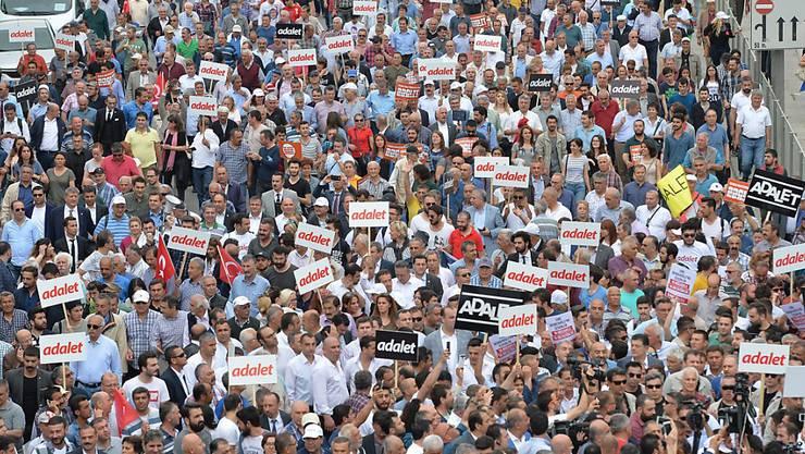 """Viele der Demonstranten - unter ihnen CHP-Chef  Kemal Kilicdaroglu - tragen einen Schild mit der Aufschrift """"adalet"""" (türkisch für """"Gerechtigkeit"""")."""