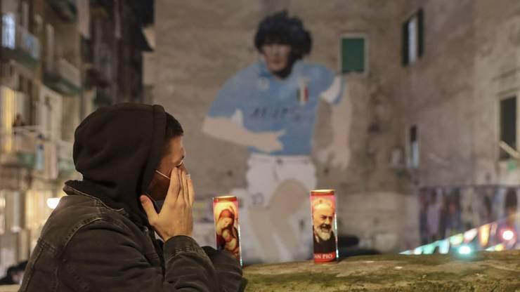 """Trauernde Neapolitanerin vor dem Wandbild des """"Stadtheiligen"""" Maradona."""