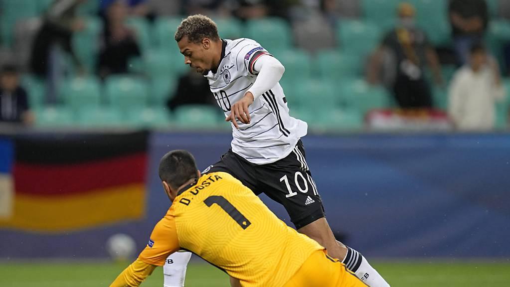 Deutschlands Lukas Nmecha umspielt den portugiesischen Torhüter Diogo Costa und erzielt das 1:0 im Final der U21-EM.