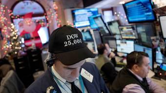 Die Mütze des Händlers in New York bezieht sich auf den neuen Höchststand des Dow Jones Index.Mark Lennihan/AP/Keystone