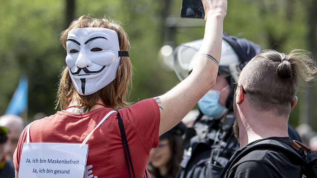 Demonstranten laufen mit einer «Guy Fawkes»-Maske auf der Straße des 17. Juni. Die Demonstranten protestieren gegen die Corona-Beschränkungen und die Änderung des Infektionsschutzgesetzes. Foto: Fabian Sommer/dpa