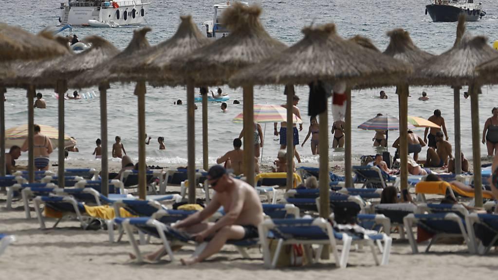 Gäste liegen am Strand von Paguera auf Mallorca. Nach der angekündigten Hochstufung Spaniens zum Corona-Hochinzidenzgebiet gibt es zunächst keine Hinweise, dass viele Menschen ihren Urlaub vorzeitig abbrechen oder gebuchte Aufenthalte stornieren wollen. Foto: Clara Margais/dpa