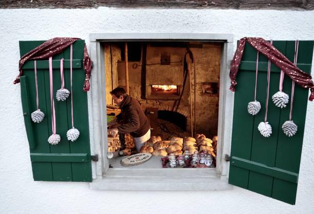 Viele Besucher kaufen ein feines Holzofenbrot. Blick auf den Holzofen in der Backstube der Landfrauen.