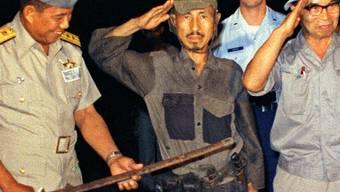 Hiroo Onoda übergibt seinen Säbel als Zeichen seiner Kapitulation dem philippinischen Präsidenten