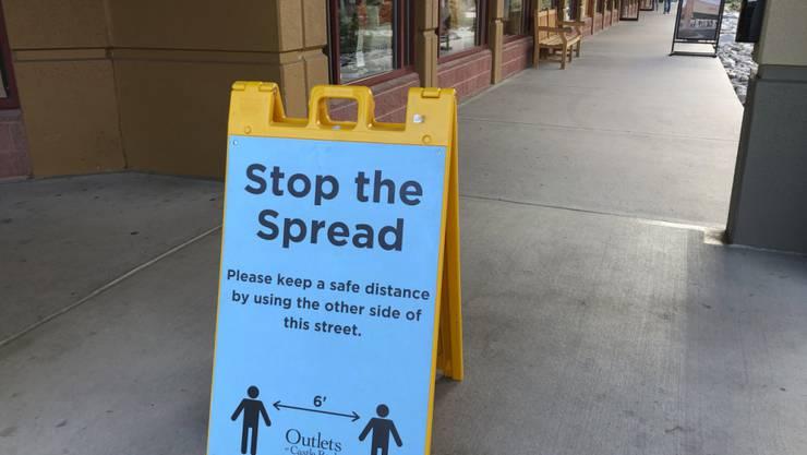 ARCHIV - Ein Schild vor einem Einkaufszentrum weist Kunden darauf hin, Abstand zu halten, um die Verbreitung des Coronavirus einzudämmen. Foto: David Zalubowski/AP/dpa