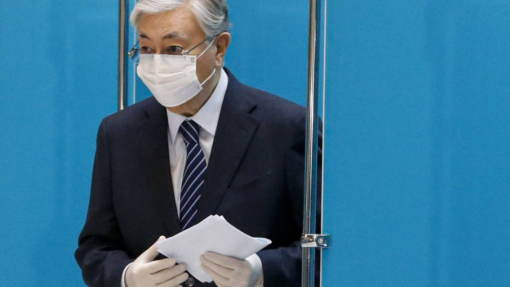 Kassym-Jomart Tokajew, Präsident von Kasachstan, trägt einen Mund-Nasen-Schutz und Handschuhe, um seinen Stimmzettel in einem Wahllokal abzugeben. Foto: Uncredited/AP/dpa