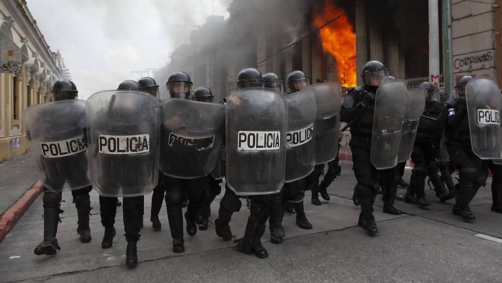 Polizisten bilden eine Blockade gegen Demonstranten. Bei Protesten gegen den Haushalt 2021 haben Demonstranten Teile des Kongresses in Brand gesteckt.