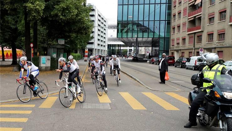 Bei der Abfahrt auf dem Basler Messeplatz begleitete am Sonntag ein ganzer Tross von Fahrzeugen und Motorrädern die 33 Velofahrer.