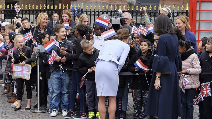 Herzogin Kate redet mit Kindern, die sie mit niederländischen und britischen Fähnchen vor dem Mauritshuis Museum empfangen haben.