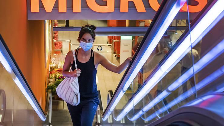 Eine  Migros-Kundin in Basel. Die Maskenpflicht wird per Montag auf weitere Orte ausgeweitet.