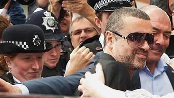 George Michael kämpft sich nach dem Gerichtsbesuch durch das Blitzlicht der Fotografen