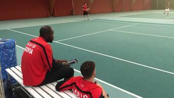 Die FCA-Verteidiger Igor Nganga (l.) und Bruno Martignoni (r.) beobachten die Tennis-Partie zwischen Patrick Rossini (hinten) und Raimondo Ponte (nicht auf dem Bild)