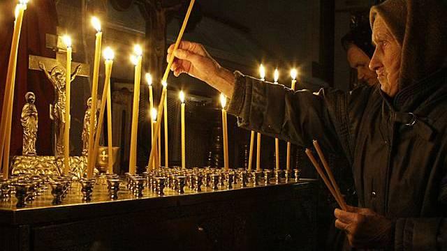 Eine Frau zündet im Gedenken an die Brandopfer in einer Kirche in Perm eine Kerze an