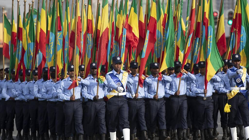 Äthiopische Polizisten, die Fahnen in den Farben der Nationalflagge halten, marschieren während einer Parade auf dem Meskel-Platz, um die neue Polizeiuniform zu präsentieren und an die Wahrung der Unparteilichkeit sowie das Respektieren des Gesetzes während der bevorstehenden Wahlen zu erinnern. Wenige Stunden vor der Wahl in Äthiopien melden die Behörden in Afrikas zweitgrößtem Land Erfolge im Kampf gegen Rebellen der Oromo-Befreiungsarmee OLA. Foto: Ben Curtis/AP/dpa