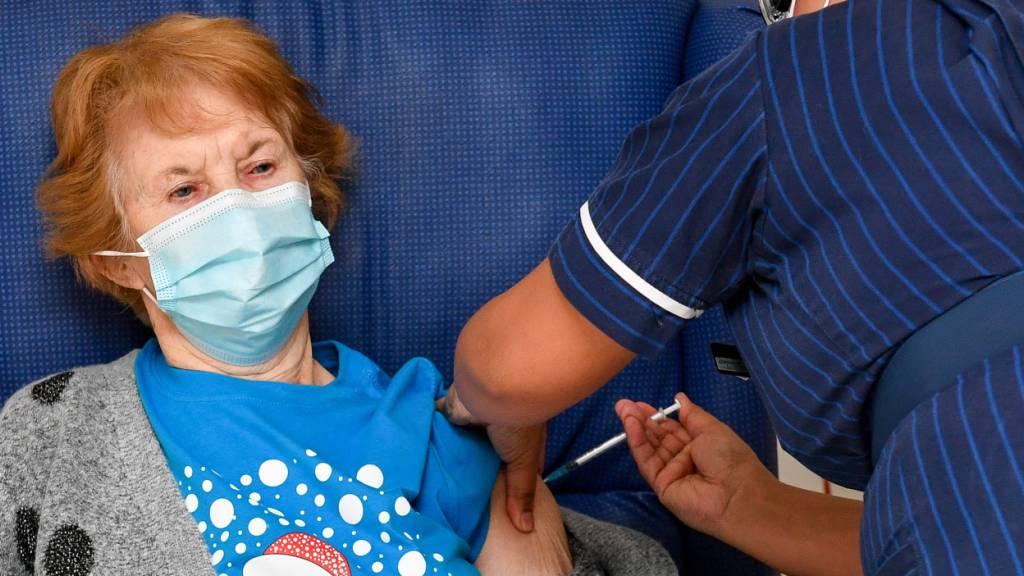 ARCHIV - Die 90-jährige Margaret Keenan (l) war die Erste in Großbritannien: Im Universitätskrankenhaus Coventry bekam sie im vergangenen Dezember ihre erste Dose mit dem Impfstoff gegen das Coronavirus. Foto: Jacob King/PA Wire/dpa