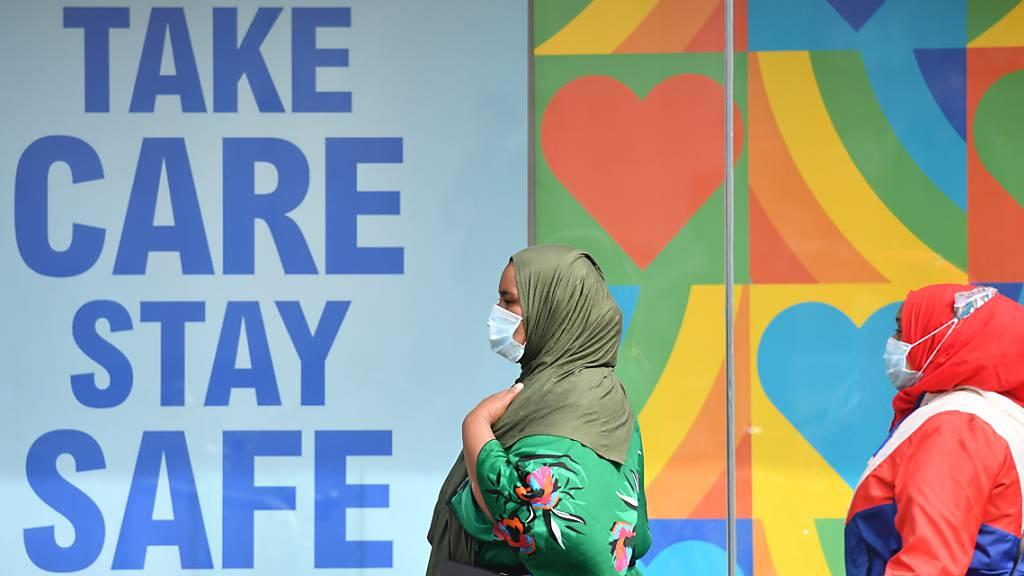 Frauen mit Kopftuch und Mundschutz gehen in einem Stadtzentrum in Großbritannien an einem Plakat vorbei, das an die Corona-Schutzregeln erinnert: «Take care, stay safe». Foto: Jacob King/PA Wire/dpa