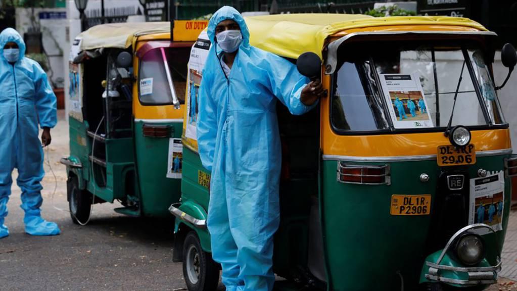 HANDOUT - In Schutzanzügen und mit Mund-Nasenschutz stehen Fahrer vor Rikscha-Krankenwagen, mit denen sie Corona-Patienten gratis durch die Hauptstadt Neu Delhi bringen. Foto: -/TYCIA/dpa - ACHTUNG: Nur zur redaktionellen Verwendung im Zusammenhang mit einer Berichterstattung über den KORR und nur mit vollständiger Nennung des vorstehenden Credits