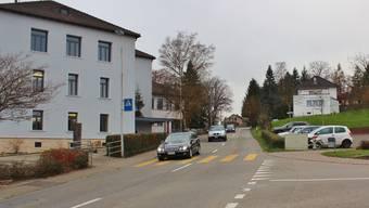 Der Vorplatz des Gemeindehauses (links) wird erneuert, der Parkplatz (rechts) erweitert – dazwischen hält der Bus.